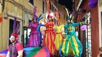 Rainbow parade on stilts by colorful stilt walkers